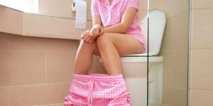 woman-sitting-on-toilet